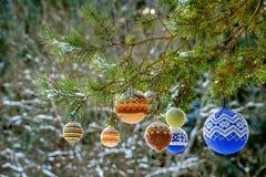 Bolas de la Navidad que cuelgan en las ramas del pino cubiertas con nieve Imágenes de archivo libres de regalías