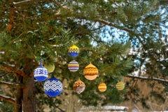 Bolas de la Navidad que cuelgan en las ramas del pino cubiertas con nieve Fotos de archivo