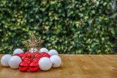 Bolas de la Navidad roja y blanca al lado de una estrella en una tabla de madera Foto de archivo