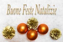 Bolas de la Navidad y de oro para los conos en la nieve, palabras italianas, Imágenes de archivo libres de regalías