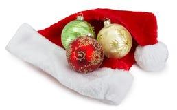 Bolas de la Navidad y sombrero del ` s de Santa Claus aislado en la parte posterior del blanco Imagen de archivo