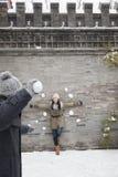 Bolas de la nieve del hombre que lanzan joven en la mujer joven en la pared Foto de archivo libre de regalías