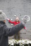 Bolas de la nieve del hombre que lanzan joven en la mujer joven en la pared Imágenes de archivo libres de regalías