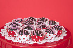Bolas de la torta de chocolate en trazadores de líneas rojos y blancos del punto en la placa roja Foto de archivo