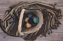 Bolas de lana hechas punto de la bufanda y del hilado en una cesta de mimbre en una madera foto de archivo
