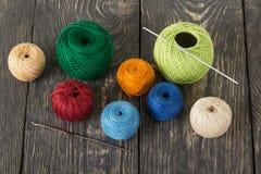 Bolas de lana multicoloras, ganchos de ganchillo en los tableros de madera oscuros foto de archivo libre de regalías