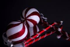 Bolas de las decoraciones de la Navidad y bastón de caramelo Foto de archivo