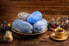 Bolas de linhas cinzentas e azuis em uma placa de madeira, um copo do chá em uns pires, em brinquedos do Natal e em agulhas de co imagens de stock