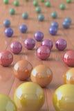 Bolas de mármol coloridas en un suelo de entarimado Foto de archivo libre de regalías