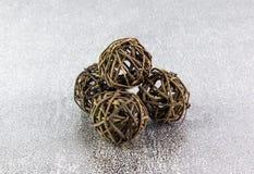 Bolas de madeira de vime decorativas em um fundo de prata Imagem de Stock