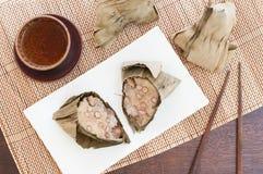 Bolas de masa hervida chinas del arroz envueltas en hojas de lámina. Imagen de archivo libre de regalías