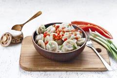 Bolas de masa hervida cocinadas en un plato de la arcilla con pimienta y cebollas fotografía de archivo libre de regalías