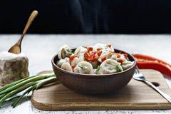 Bolas de masa hervida cocinadas en un plato de la arcilla con pimienta y cebollas fotos de archivo