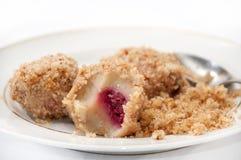 Bolas de masa hervida con las migas y las cerezas de pan con una cuchara en un blanco Foto de archivo