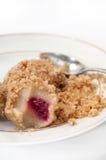 Bolas de masa hervida con las migas y las cerezas de pan con una cuchara en un blanco Imagen de archivo