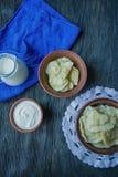 Bolas de masa hervida con las patatas y la col Crema agria, leche y verdes Plato tradicional de Ucrania Fondo de madera oscuro imagenes de archivo
