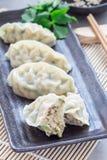 Bolas de masa hervida coreanas cocidas al vapor Mandu con la carne y las verduras del pollo en la placa negra, vertical Foto de archivo