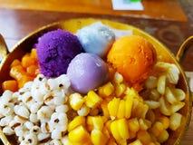 Bolas de masa hervida del sésamo y purés de patata púrpuras dulces en el cuenco de cobre amarillo fotografía de archivo