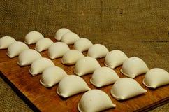 Bolas de masa hervida en casa en tabla de cortar de madera Imagenes de archivo