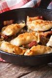 Bolas de masa hervida fritas calientes con tocino y cebollas en una cacerola, vertical imagenes de archivo