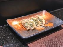 Bolas de masa hervida de Gyoza en el pote de arcilla hermoso del plato imágenes de archivo libres de regalías