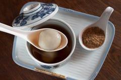 Bolas de masa hervida negras del sésamo en Ginger Tea en cuanto al postre chino foto de archivo