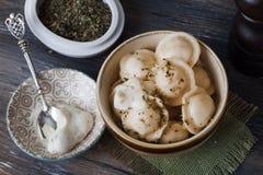 Bolas de masa hervida, raviolis, tortellini, cuenco del pelmeni, salsa verde oliva de la hierba, cucharas de plata, aún vida de m Imágenes de archivo libres de regalías