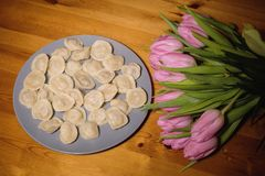 Bolas de masa hervida y un ramo de tulipanes rosados en un fondo de madera Imagen de archivo libre de regalías