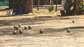 Bolas de metal e bola de madeira alaranjada na terra no parque local fotos de stock