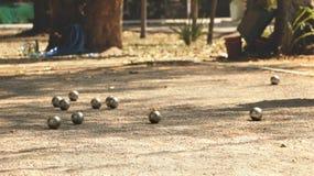 Bolas de metal y bola de madera anaranjada en la tierra en parque local fotos de archivo