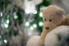 bolas de neve dos abraços de urso da peluche com a árvore de Natal azul e luzes borradas no fundo Fotografia de Stock Royalty Free