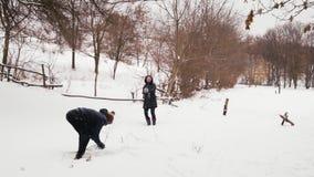 Bolas de nieve indias del tiro del individuo y de la muchacha en el bosque almacen de video
