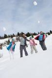 Bolas de nieve que lanzan de la familia joven el vacaciones del invierno imagen de archivo