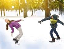 Bolas de nieve que lanzan del muchacho y de la muchacha Foto de archivo