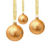 Bolas de oro colgantes de la Navidad con la cinta aislada Fotos de archivo