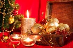 Bolas de oro de la Navidad en una caja de madera y velas Composición del Año Nuevo Imagen de archivo