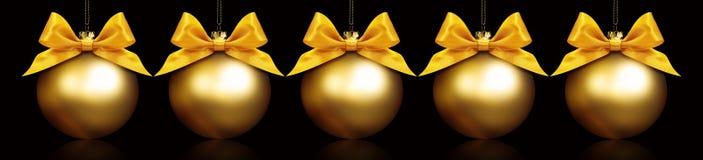 Bolas de oro de la Navidad que cuelgan en fondo negro Imagen de archivo