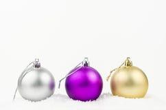 Bolas de oro, de plata y púrpuras de la Navidad en la parte posterior del blanco Fotografía de archivo libre de regalías