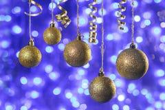 Bolas de oro en un fondo azul brillante Bokeh bajo la forma de luces azules redondas Fotografía de archivo libre de regalías