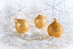 Bolas de oro de la Navidad en un fondo hermoso con los copos de nieve Foco selectivo Foto de archivo