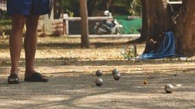 Bolas de Petanque e bola de madeira alaranjada na jarda da rocha com um homem que está na máscara - Sunny Day no parque fotografia de stock royalty free