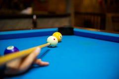 Bolas de piscina en la mesa de billar azul del fieltro con las manos del jugador y el palillo de taco de billar Deportes interior Imagen de archivo libre de regalías