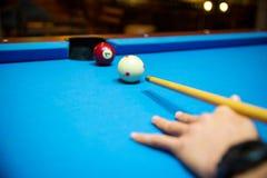 Bolas de piscina en la mesa de billar azul del fieltro con las manos del jugador y el palillo de taco de billar Deportes interior Fotografía de archivo