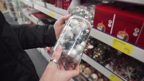 Bolas de plata para el árbol de navidad en manos femeninas Preparación para los días de fiesta del Año Nuevo, selección del Año N almacen de metraje de vídeo