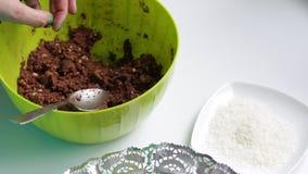 Bolas de rollos de una mujer fuera de la mezcla preparada, para cocinar los dulces del chocolate con la aspersión movimientos almacen de video