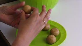 Bolas de rolos de uma mulher dos biscoitos com leite condensado em suas mãos As bolas prontas estão na placa Cozinhando princ?pio filme