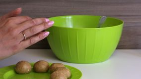 Bolas de rolos de uma mulher dos biscoitos com leite condensado em suas m?os As bolas prontas põem sobre uma placa Cozinhando pri vídeos de arquivo