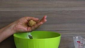 Bolas de rolos de uma mulher dos biscoitos com leite condensado em suas m?os As bolas prontas p?em sobre uma placa Cozinhando pri video estoque