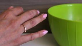 Bolas de rolos de uma mulher dos biscoitos com leite condensado em suas m?os As bolas prontas p?em sobre uma placa Cozinhando pri filme