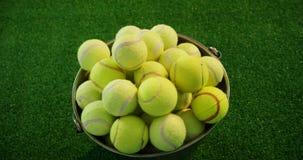 Bolas de tênis na cubeta no estúdio 4k video estoque
